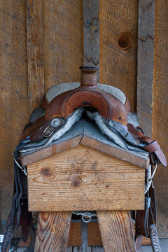 Worn comfortable leather western saddle on a wood saddle stand against a rustic wood wall