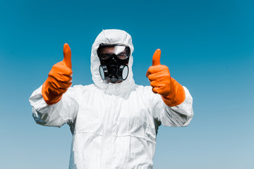 exterminator in protective mask and uniform standing and showing thumbs up