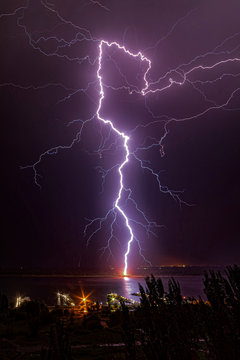 Night lightning strikes the pier on the opposite bank of the river