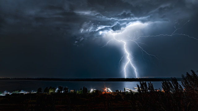 Lightning strike in the night sky above the river