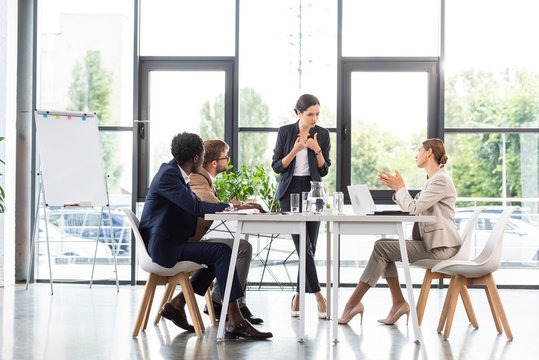 multiethnic businesspeople sitting at tables during conference in office