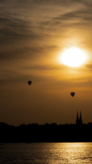 Helsinki summer sunset. Balloons glide through evening sky with a city skyline in the background.