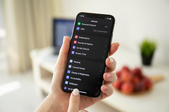 Woman hand holding iPhone X with IOS 13 Dark Mode