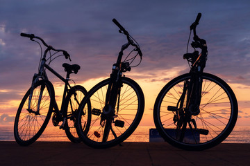 The silhouette of bikes on the beach with sunset cloudy sky background