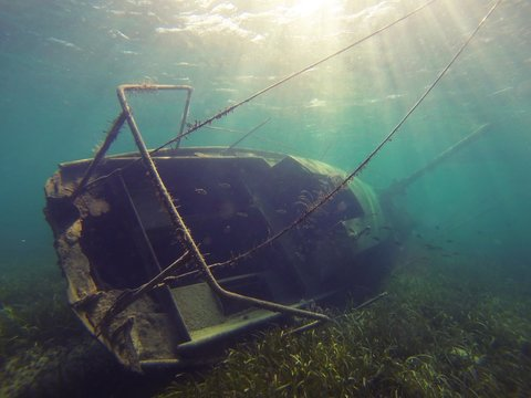 Underwater shot of a wrecked rusty sailboat with seaweed growing on it
