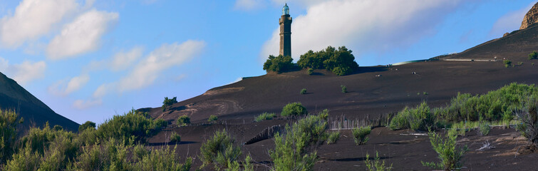 Panoramic shot over the eerie looking volcanic lava landscape with the abandoned iconic lighthouse inmidst ashes sand at Ponta Dos Capelinhos, submerged in an eruption in 1957, on Faial Island, Azores Fototapete