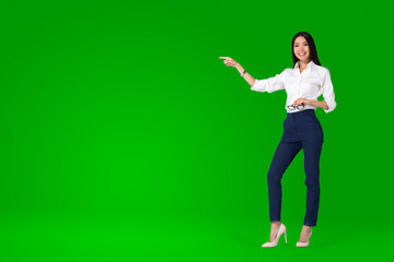 A beautiful young asian woman, anchor or tv presenter is getting filmed inside a green screen chroma key studio to create a video with removable background that can be replaced