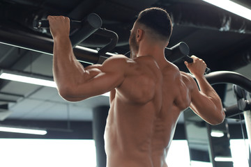 Fit and muscular man pulling up on horizontal bar in a gym.