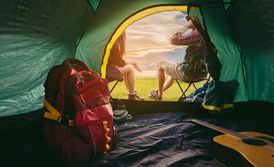 Tuinposter Kamperen Couple lifestyle travel camping together in forest, Happy and relax young man and woman sitting on chairs near tent with backpack,guitar looking mountain river romantic traveling