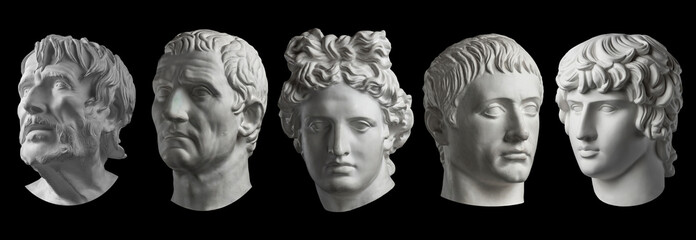 Five gypsum copy of ancient statue heads isolated on a black background. Plaster sculpture mans faces.