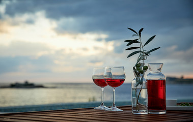 two glasses of rose wine with  olives against blue water on a pier..