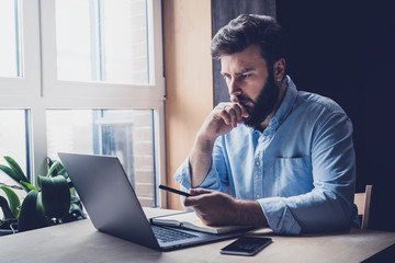 Professional sitting in office in front of laptop. Developer thinking on solutions for work. Home-based student getting distant education. Young serious bearded man in blue shirt working on desktop.