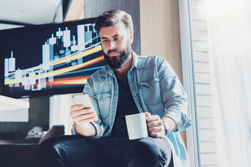 Office manager having break, relaxing at workplace. Man using smartphone for online communication in social media. Guy texting in networks, reading updates, sharing. Male person dialing phone number