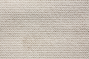 Knitted material background in light tone.