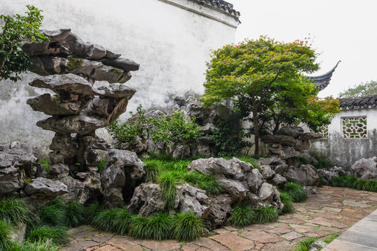 A corner with rock work, tree and grass  in Master of the Nets Garden or Wangshi Garden in Suzhou, China, among the finest gardens in China and UNESCO World Heritage Site.