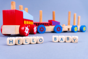 """Letters in the front saying """"Hello Baby"""", a colorful wooden train in the back - newborn concept"""