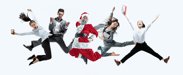 Happy Christmas Santa Claus jumping with office workers on white studio background. Caucasian male model in traditional holiday's costume. Concept of holidays, new year's, winter mood, gifts