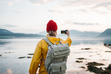 Traveler wearing yellow raincoat taking photo by smartphone fantastic nord landscape while traveling scandinavia. Man tourist takes a photo great mountain nature