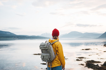 Hipster traveler wearing backpack and yellow raincoat looking away at mountain and fjord. Alone man traveling at scandinavian authentic landscape