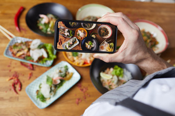 Closeup of unrecognizable man taking photo of delicious Asian food set on wooden table in cafe or restaurant, focus on smartphone screen, copy space