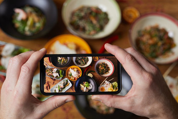 Close up of unrecognizable man taking photo of delicious Asian food, focus on smartphone screen, copy space