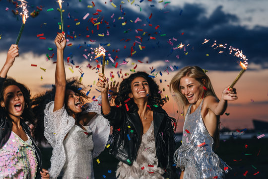 Group of four happy women dancing with sparklers under confetti at sunset