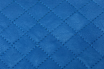 Blue quilted leather texture or background, closeup