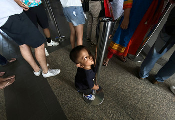A boy stands as their parents line up for a ticket, at a train station in Bangkok