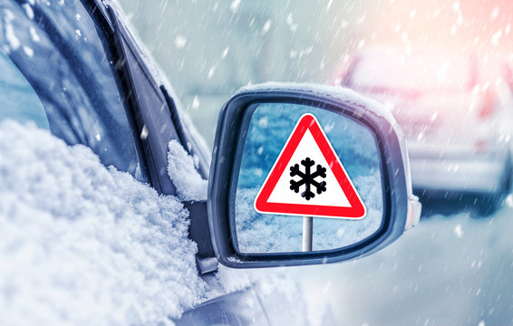Winter driving - warning sign - risk of snow and ice. Winter driving - caution. Black Ice. Concept of snow in the road. Car hit a snowstorm. .Reflection of a road sign in a car mirror