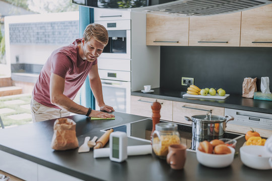 Cheerful man cleaning his kitchen after cooking