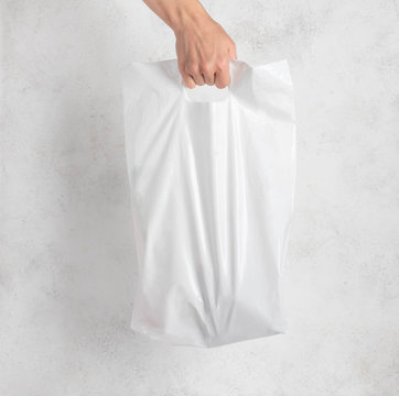 white plastic bag held by a woman's hand. light background.