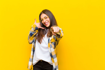 young  pretty woman smiling cheerfully and pointing to camera while making a call you later gesture, talking on phone against orange wall