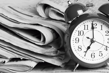 Alarm clock and Newspapers on the desktop in the office.
