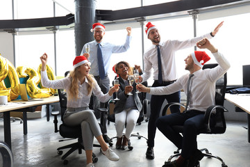 Business people are celebrating holiday in modern office drinking champagne and having fun in coworking. Merry Christmas and Happy New Year 2020.