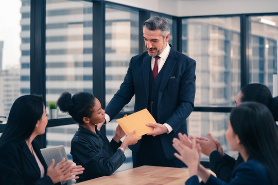 Company leader giving bonus to the employee who is working with high quality of performance. The business coworker is slapping to congratulate to his teammate for being promoted as manager.