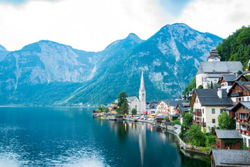 Scenic view of famous Hallstatt lakeside town reflecting in Hallstattersee lake in the Austrian Alps on a sunny day in summer, Salzkammergut region, Austria