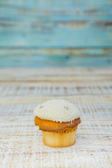 Tasty cupcake on wooden table on vintage background