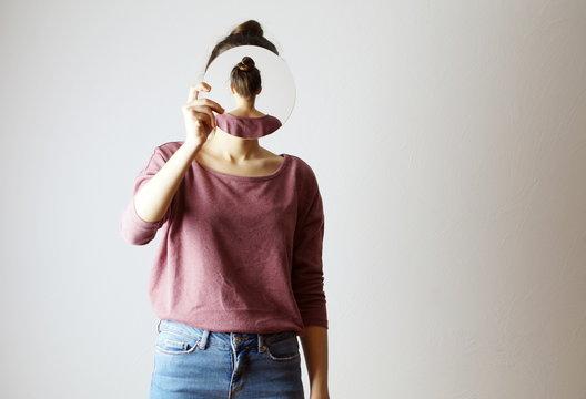 wer bin Ich? Frau, die einen Spiegel vor ihr Gesicht hält. Gesichtslos, Identität nicht erkennbar