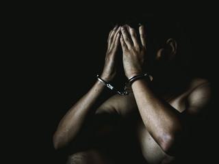 Young man desperate to catch the iron prison,prisoner concept,Handcuffed hands of a prisoner in prison, Male prisoners were severely strained in the dark prison, violence,