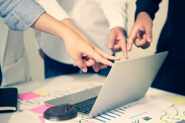 Concept teamwork and partnership, the picture of many fingers voting and pointing on the laptop screen shows the conclusion of the meeting, background with the chart on the table in a vintage tone.