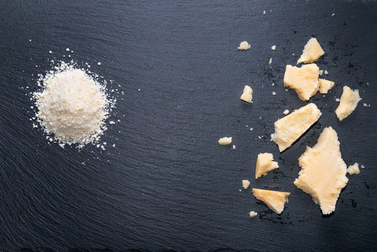 top view of tasty fresh pieces cheese and grated parmigiano on black slate background