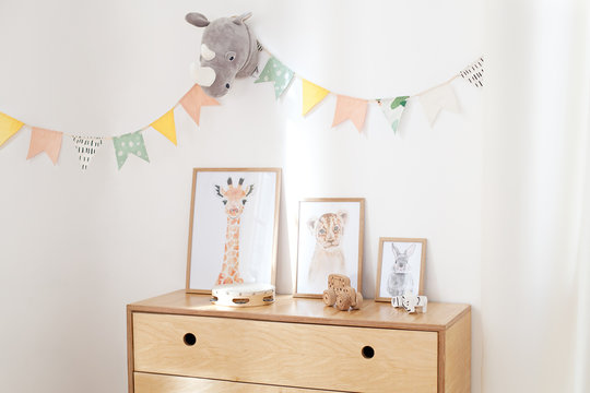 concept of a cozy interior, housewarming. Photo frames on a wooden chest of drawers near a white wall. white wall is decorated with multi-colored flags for children near dresser in the children room