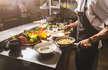 Professional chef cooking in the kitchen restaurant at the hotel, preparing dinner. A cook in an apron makes a salad of vegetables and pizza. Wall mural