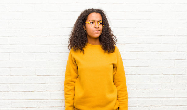 young black woman looking puzzled and confused, wondering or trying to solve a problem or thinking against brick wall