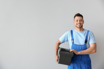 Portrait of handsome plumber with tools box on white background