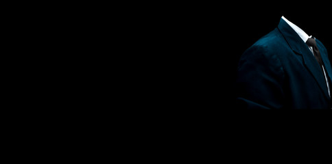 Faceless unrecognizable male wearing a blue colored suit with a black necktie and standing against a black background with good positive attitude. Wide-angle full resolution image.