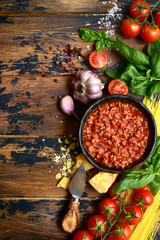 Homemade italian bolognese sauce with ingredients for making. Top view with copy space.