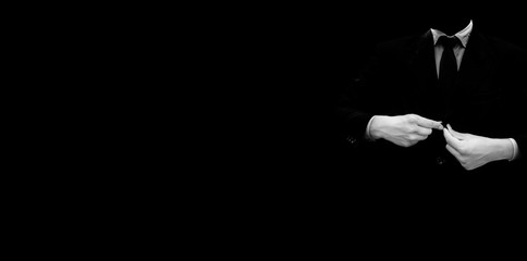 Faceless businessman or an employee or worker buttoning his suit buttons isolated against a black background. Wide-angle high-resolution image.