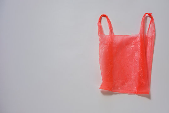 Crumpled red plastic carrier bag on grey