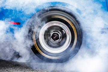 Drifting car. Drag racing car burns rubber off tires before the start